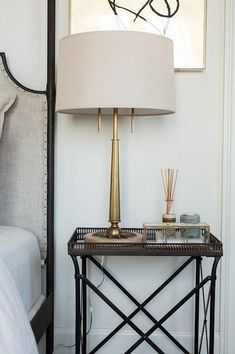 Chic bedroom boasts a gray linen headboard on 4 poster bed next to a metal mirrored tray top bedside table and an antique brass lamp.