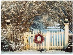 Christmas wreath on white picket fence in snow