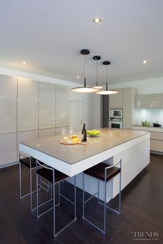 High-gloss lacquered cabinets in the Poggenpohl kitchen bounce light back into the room. The tall bank of cabinets incorporates an integrated fridge-freezer and a pull-out pantry. There is also a pull-out unit next to the ovens.