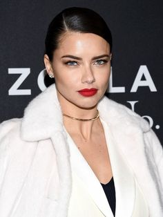 Adriana Lima stuns with a sleek, pulled back bun, perfect brows, and a matte red lip