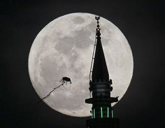 The full moon rises behind a mosque as a kite flies in Amman