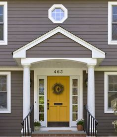 golden yelloow front door on a dark gray or taupe house is beautiful