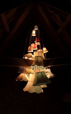Cute chandelier-like effect, made from individual lamp shades in varying sizes and hung, cascade style, at differing heights.  Cute for a romantic bedroom, or maybe outdoor, special-event lighting?