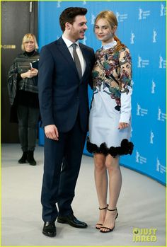 Richard Madden & Lily James in a Mary Katrantzou dress, Jimmy Choo sandals, and Dior earrings.