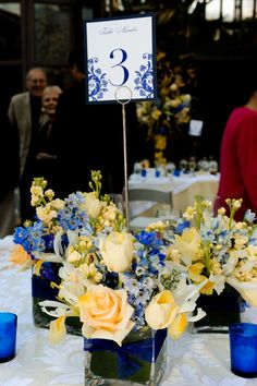 yellow and blue arrangements in clusters of clear square vases lined with leaves & a blue ribbon tie. Designed by www.anikdesigns.com at Callaway Gardens in the Spring!