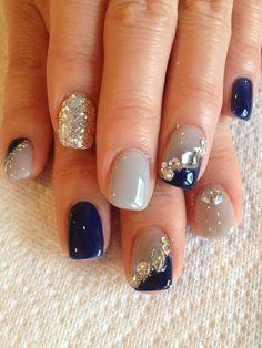 Uñas de una chica pontadas en color azul con café y piedras