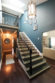 A metallic pendant light adds a little glitz to this peacock blue foyer. Painted stairs introduce more color to the vaulted entryway.
