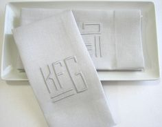 "quartz grey guest towels with 2"" border and tone on tone block monogram."