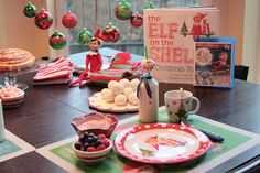 Elf Arrival Breakfast:  set table with snowmen dishes, elf video and basket of wrapped Christmas books.