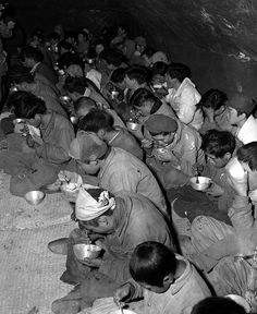 Communist guerrillas and their families, captured and brought down from Mt. Chirisan, by elements of the ROK Captiol Division, are fed in the POW stockade, Kurije, Korea. December 12, 1951. Cpl. Paul E. Stout. (Army)