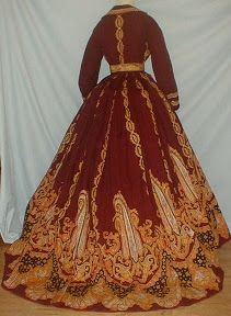 "Brilliant Paisley Print 1860's Dress-magnificent burgundy cashmere wool paisley print dress w/ documentation. Note reads ""Paisley dress worn by Grandma Eckert at mother's wedding.""  Paisley pattern in shades of orange, blue and black.  Dress has original paisley print belt. Armscyes and neck are piped; bodice lined w/cotton has hook & eye closure. Front button closure to mid hip. Unlined skirt has cotton hem facing. Excellent condition.B 34 W 24 Fr skirt length 40 Back length 51."
