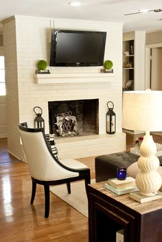 White painted brick fireplace with wall-mounted TV. #LTDH