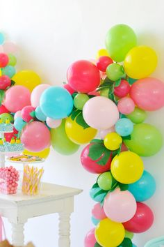 Aqua, lime green, yellow, hot pink, and light pink balloon birthday party garland. Large and small balloons. Summer palm leaves. Colorful birthday party decor. Flamingo Party styling by Happy Wish Company. Photography by Tammy Hughes Photography. Stationery by Minted artist, Laura Hankins.