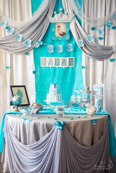 We chose to go with a turquoise, white,silver and tinge of green color theme.The Cake table was covered in grey tablecloth with turquoise and silver