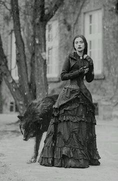 Appears to be young Victorian Gothic lady ..and seemingly tame wolf..maybe a different version of the fairytale ''little red riding hood..she is not wearing a cape with a hood ..she is out in the snow just in her long dress but I like it..it's so vintage ..as if the Brothers Grimm actuall met her and then wrote the story xo