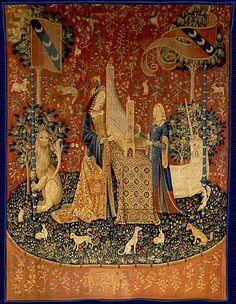 OÍDO (La dama y el unicornio)   La dama toca un ÓRGANO PORTÁTIL sobre lo alto de una mesa cubierta con una alfombra turca. Su doncella está en pie, al otro lado, y opera el fuelle. El león y el unicornio de nuevo están enmarcando la escena sosteniendo los banderines. Lo mismo que en los demás tapices, el unicornio está a la izquierda de la dama y el león a la derecha - un común denominador de todos los tapices.