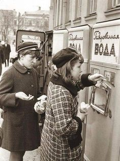 Young people buying a soda drink at the soda vending machine. Sparkling water was mixed with sweet syrup. Back in the USSR. 60's. Vintage photo.