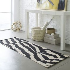Get grounded with graphics. Durable, handcrafted jute gets a fun update with a striking screen-printed design. This rug plays well in a classic black-and-white room and brings personality to a neutral small space.