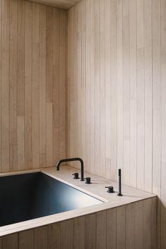 Light wood paneled bathroom with dark green tub.
