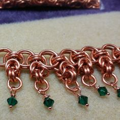 "This link is to my Google+ post which shows additional pictures.  This necklace is made of 18 gauge copper rings, 9/32"" ID for the large rings and 5/32"" ID for the small. The green crystals hang from a byzantine unit on the helm weave and a simple 2-2 chain in the smaller ring size is used for the attaching chain.  It's surprisingly heavy and should hang nicely at a little less than 18"" total length."