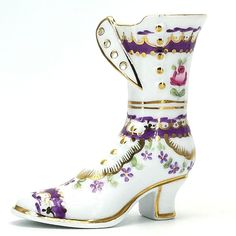 Pre-owned decorative collectible glazed porcelain ceramic slipper or shoe.  The white ladies Victorian style button up high top shoe figurine is decorated with a purple and gold floral design and scalloped accents.