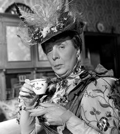 Dame Edith Evans, DBE (1888-1976) has a cuppa, as Lady Bracknell in Oscar Wilde's 'The Importance of Being Earnest'