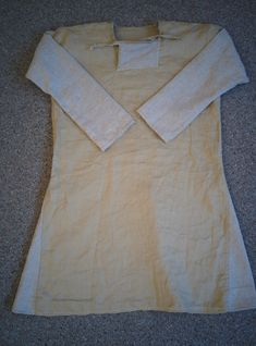 New linen undertunic based on find from Viborg. Also made from leftover cloth. Square neckhole with side-slit, tied with strings. Torso is two-piece sewn at shoulder.