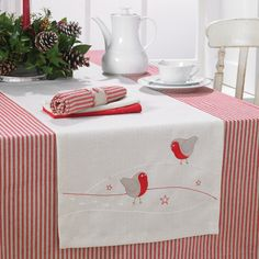 Add a finishing touch to your Christmas dinner table with this charming embroidered robin table runner.At each end of the runner there are two pale grey robins with a red underbelly.There is also pretty white and red embroidery detail finished with three tiny red stars. This is something that can be brought out year after year and would also make a lovely gift for a hostess.