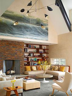 All About Architecture - Style: Modern This large brick fireplace's unique design features extend toward the ceiling and also form the base of a seating unit and a bookshelf. The elevated hearth extends around the room and serves as the base for an L-shape couch.