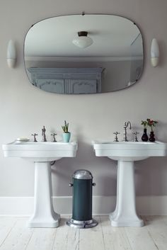 Double pedestal sinks in bathroom, diffuse ceiling light with sconces on either side of mirror | Remodelista