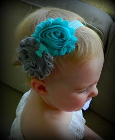 Turquise/Teal and gray shabby flowers with a crystal bow in the center. Attached to a white and Turquoise CHEVRON elastic band! Great price and low shipping!
