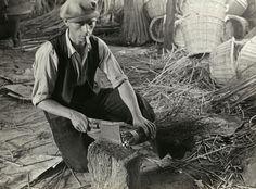 Bezembinders; oude ambachten. Een bezembinder hakt de twijgen voor de te maken bezem gelijk op een hakblok met een hakbijltje, temidden van manden in de werkplaats. St. Willebrord, 1934.
