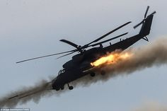 A Mil Mi-35 attack helicopter darts downwards while firing missiles. Clouds of…