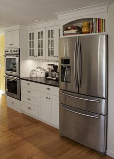 Kitchen remodel by Renovisions. Soapstone countertops, hardwood flooring, white cabinets, stainless steel appliances.