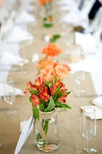 Orange flowers in mason jars to dress up the table.