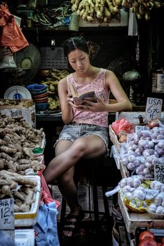 Hong Kong Markets - YAU MA TEI, HNG KONG - JULY, 4: A young woman reads a book at her market stall in Reclamation Street, Hong Kong on July 4, 2014.