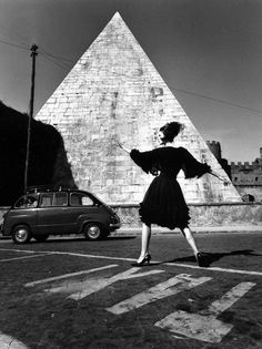 Dorothea McGowan poses with pyramid wearing a dress by Capucci, Rome, 1962. Photograph by William Klein. From 1955 to 1965 Klein worked for Vogue. He preferred to photograph his models out in the street or on location. He used this opportunity to introduce new techniques to fashion photography, including the use of wide-angle and long-focus lenses, long exposures combined with flash and multiple exposures – making fashion an area of innovation in photography.