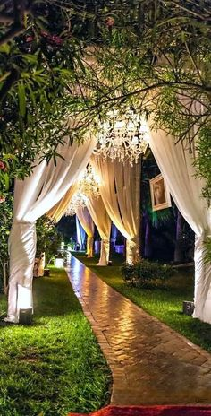 Dreamy and romantic wedding decor. Chandeliers, cortinas y flores colgantes sobre el camino central hacen de los jardines para bodas un cuento de hadas. #weddingdecoration