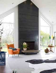 The airy living room is dominated by a massive steel fireplace on the northern wall with windows on either side overlooking the lawns. Industrial Fireplaces, Metal Fireplace, Linear Fireplace, Farmhouse Fireplace, Home Fireplace, Fireplace Remodel, Fireplace Surrounds, Fireplace Design, Modern Fireplaces