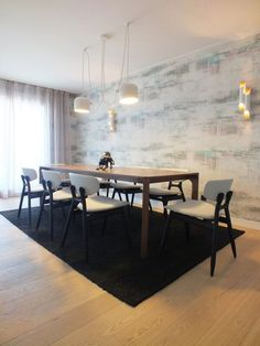 AIM pendant lighting shines in this sunlit, spacious dining area featuring a black carpet, dark wooden table and light hardwood floors.