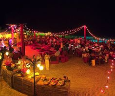 Multi-colored string lights compliment the relaxed, beachy feel for this outdoor wedding reception.
