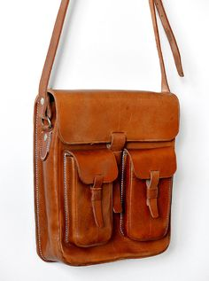 This handsome, vintage 1970s, amber-toned brown, structured-leather, contrast-stitched, 8 hole adjustable strap, shoulder satchel would make a fantastic work or travel companion. Highly durable and extremely well-made. This bag is in excellent vintage condition. There are some natural marks in the leather but they seem to be due to the nature of the leather rather than wear and tear. They dont in anyway take away from the overall beauty of the item. The contrast stitch is a nice off-white…