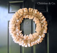 Old dictionary pages folded up into simple fan shapes and woven through a metal wreath form