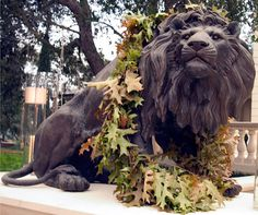 A lion statue is decorated with floating candles and a garland of leaves.