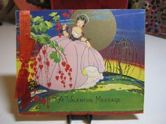 Gorgeous art deco colorful gold gilded 1930's Valentines card lady in elaborate  gown walking past tree w/ hanging red hearts silk ribbon