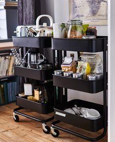Dois carrinhos de cozinha repletos de comida, uma torradeira, uma cafeteira elétrica e café