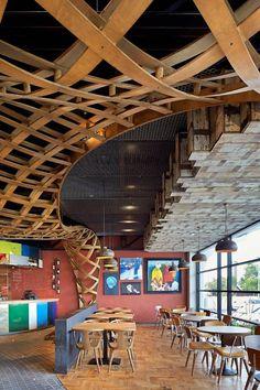倫敦餐廳「Nando's Loughton」前身是加油站與汽車經銷中心,所處的位置在十字路口的角落,承襲過去汽車展銷中心的圓弧形的建築樣貌,對於餐廳來說擁有非常棒的環境條件,但對設計者來說,必須要克服基地形狀造成動線與座位安排的困擾,同時因應地理位置,必須運用創意的設計搶攻行人的眼球,才能成為十字路口的視覺焦點。 在全倫敦都有據點的Nando's Loughton餐飲集團將此空間交由STAC建築設計事務所操刀,為了呼應基地的弧形曲線,建築師運用流動的線條結構主導空間視覺,藉由石頭磚鋪排出的流動曲線在地板設計出前往點餐櫃檯的動線,與用餐區的木地板形成明顯的分隔,天花板也使用相同的流線語彙,與地板動線相呼應。蜿蜒的木結構是整體空間的視覺焦點,宛若彩帶編織的木結構使空間表情更立體。 via STAC Architecture & BuckleyGrayYeoman