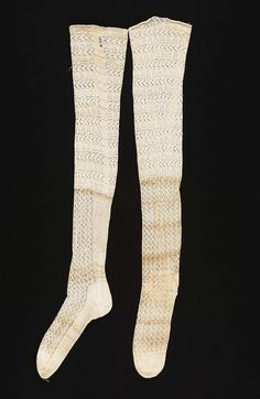 Pair of stockings, 18th century. White cotton knitting, instep and lower leg in vertical stripes of fancy stitches, upper leg in horizontal stripes of fancy open-work stitches, initial: S, and symbol embroidered in black silk in cross stitch on top of stockings.