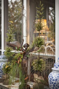 When we decorate my courtyard for my Holiday Open House ever year, I like to make a big splash on the console table that nestles up against the wall of my screened porch. I don't want anything too heavy in this in-between place because I don't want the tabletop display to block the view from the screened porch. Yet, the display needs to be tall, full and gutsy or it will get lost in the vastness of the courtyard. This year's display struck the perfect middle ground. We started with a darling gar
