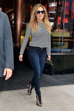 Jennifer Lopez plays up the classic jeans and striped t-shirt with an edgy pair L.A.M.B. sandals and Thierry Lasry cat-eye sunglasses.